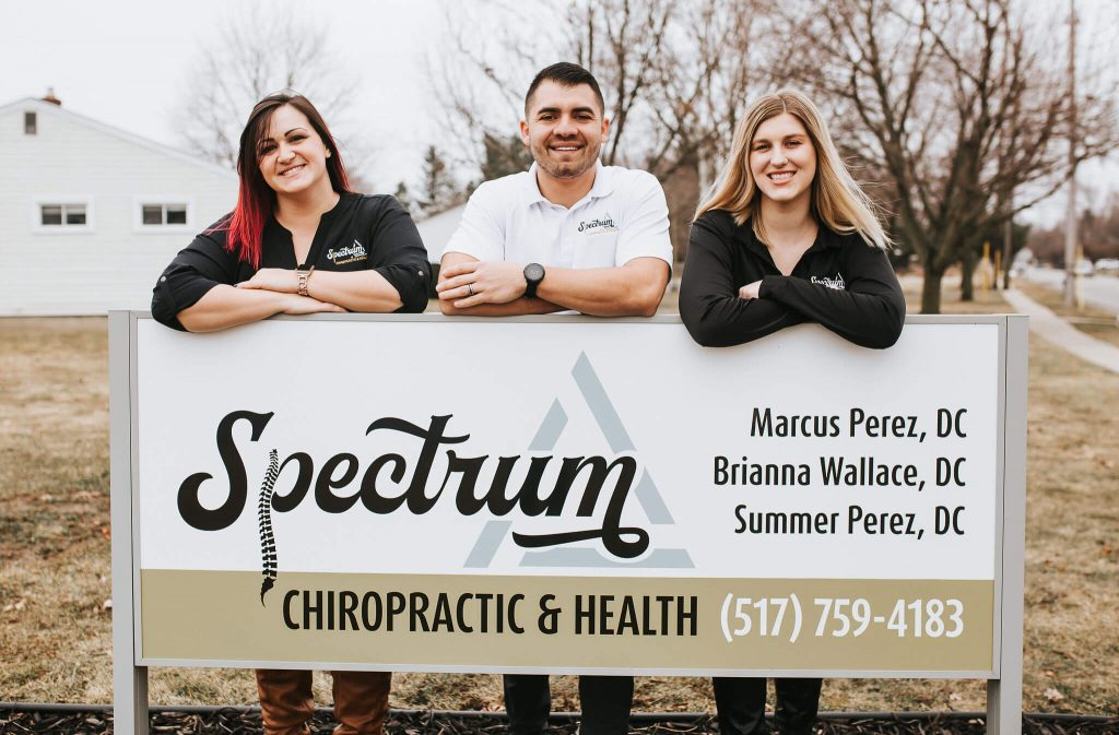 Three Doctors of Chiropratic at Spectrum Chiropratic & Health standing outside behind business yard sign.