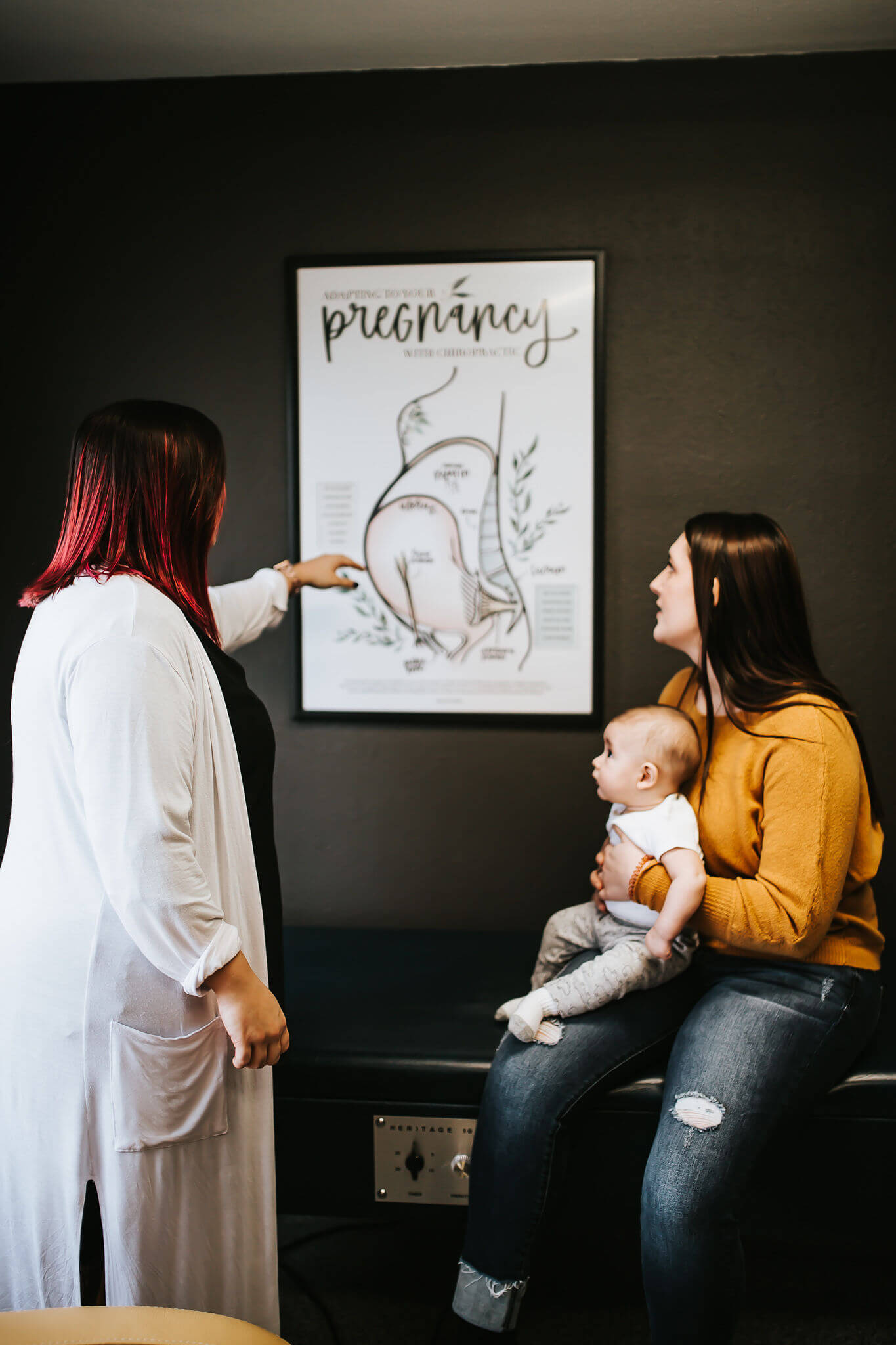 Spectum Chiropractic and Health Doctor, Brianna Wallace, pointing to a pregnancy diagram while a female patient holding her baby listens.