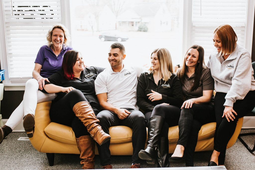 Six Spectrum Chiropractic and Health staff sitting on a couch smiling.