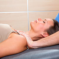 Myofascial technique with therapist hands on a womans shoulders.