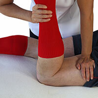 Male massage therapist performing Neuromuscular technique on a male patient.