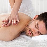Female Massage Therapist performing massage technique on a male patient.